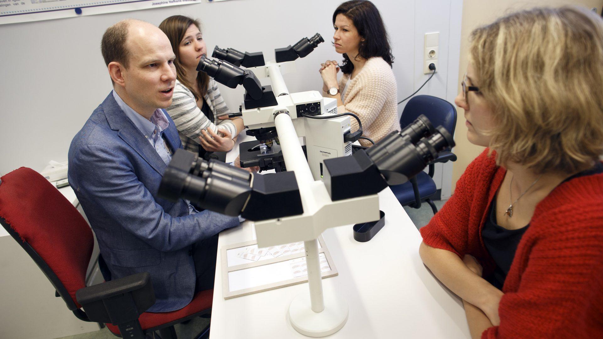 neuroloog Titulaer onderzoekt patiëntenmaqeriaal onder microscoop